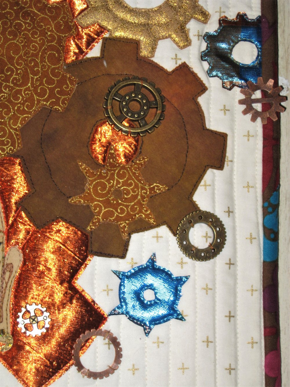 The background fabric was selected because it looked simple with a hint of gold and it also appeared old fashioned. I used two lames, a leather-like lame, gold embossed fabrics and rusty looking brown for the gear fabrics. I purchases metal gears from two different stores and hand sewed them sporadically to the quilt.