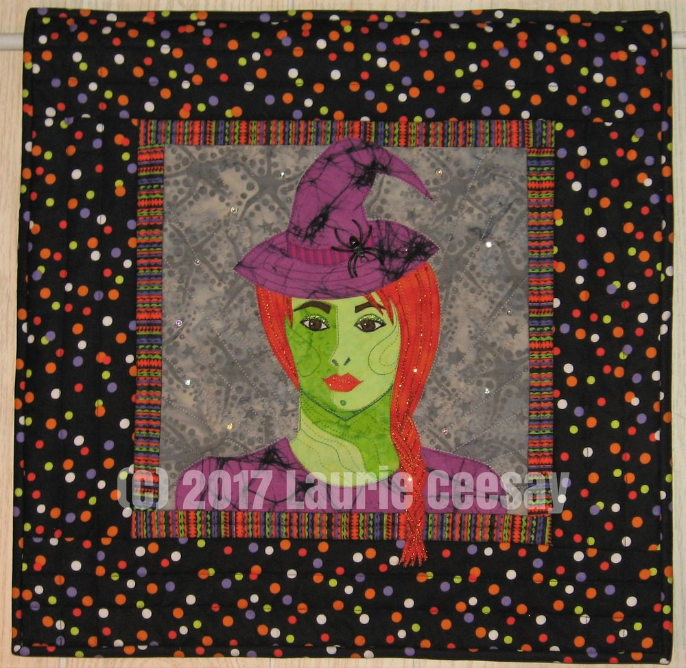 "My first portrait quilt pattern designed in 2011, originally titled ""Angelina"" then changed to ""Whimsical Selfie Quilt"" for marketing sake, got a new version. I continue to add different hairstyles, hats and holidays. Since I am a huge Halloween and witch lover it seemed normal to add a witch selfie quilt. I made the top a year ago and I am not a UFO fan so I thought I needed to complete this wall hanging.   I have a love of collecting Halloween fabrics and digging into my fabric stash to make this was a breeze. I selected the one sided long hair braid for the hair and added the basic dress pattern instead of the usual shoulder straps-its colder in the fall so she needed more clothes!"