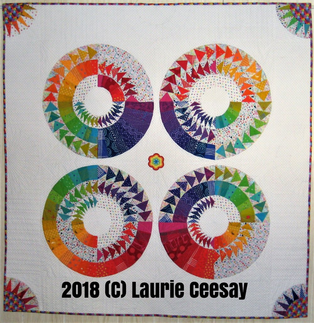 "The International Quilt Festival is having a quilt contest debuting at the April 2018 quilt show called The Celebration of Color. There are three categories-traditional, modern and art. I entered a quilt last year in the modern category and it made the cut. IQF also chose to have the exhibit on display at the Houston show last November which was an honor. This time around I was inspired by a traditional New York Beauty block. I found a new book recently by accident on Pinterest called ""New York Beauties & Flying Geese"" by Carl Hentsch. I loved the combo of New York Beauty blocks and curved flying geese. The version I selected used 32 different colors which excited me because I love scrappy quilts and I was again feeding my OCD for color order and the color wheel!! I used fabrics from my stash which were not used from some other quilt I never made plus I added some of the new Alison Glass Chroma fabrics!! They are so lovely!!  This is paper piecing and one must psych up for the mess of the paper removal! The curved flying geese blocks ended up small and pinning and matching two sizes of flying geese on a curve proved to be a challenge. Each block was 20"" and the rules state the minimum size is 48."" I added a 6.5"" border of white background fabric and each border got a simple New York beauty block using a rainbow of colors to repeat the motion of color. It is 51.5"" square.  I added a multi colored print for the centers and I also used it for the binding. It has circles which repeated the circles in the New York Beauty blocks. I titled the quilt ""Pinwheels"" because when they blow in the wind they are round, colorful and have movement just like the blocks in this quilt!!"