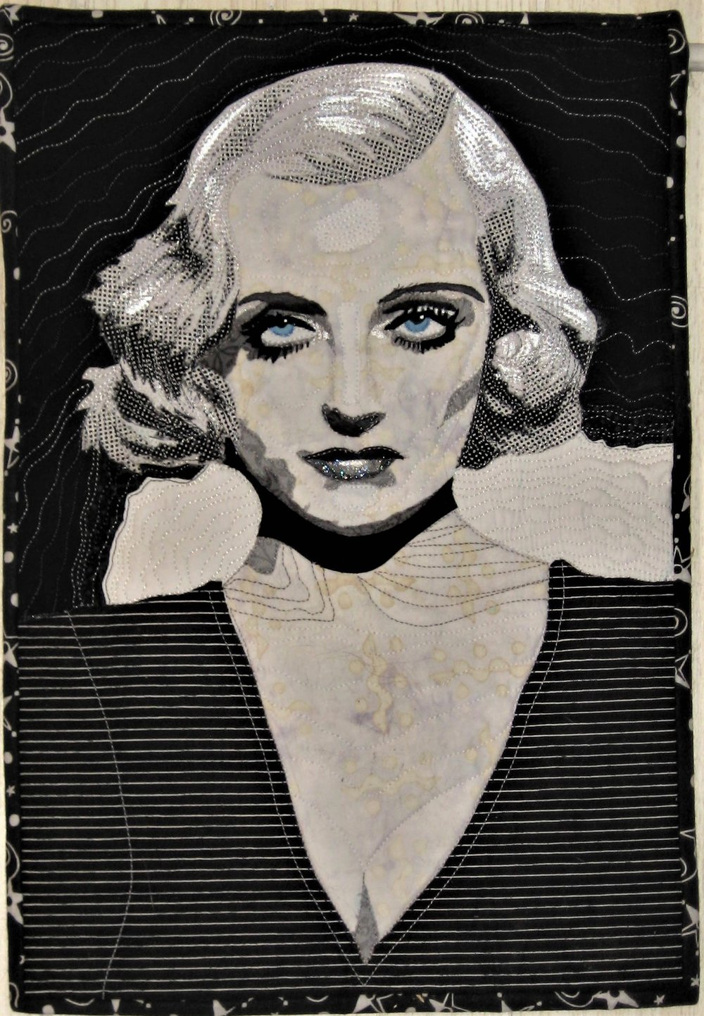 "Today is reveal day for my Facebook art quilt group Art Quilts Around The World. The challenge was titled Film Noir and I did not know this subject until I Googled it. It represents the Black and White movies of the 20s-30s when the movie industry was in its infancy. Plenty of dark smoky rooms, everyone was smoking cigarettes, shadows, interestingly textured backgrounds, dark street scenes and, my personal favorite, femme fatales!! They were the actresses who became famous from the movies they were in-Bette Davis, Carole Lombard and Myrna Loy to name a few. Sorry but no cigarettes in my quilts!  I saw this challenge as a study of value and chose to work in black and white with the exception of using a light icy blue for the irises in my portrait quilt. I found a photo where the bleach blonde finger waves caught my attention. This was my challenge to create a 3D image on a flat surface and capture the way the light or lack of light hit the waves in the hair.   I was not sure if I wanted to create a value scale from white to gray to black OR use prints and go from white to a white print with black to a black print with white to solid black. I chose both-grays for the skin tones and the prints for the hair. I collect white batiks and they are difficult to come by. I had a pile or ""warm"" whites for the skin tones and ""cool"" whites for the hair. I used as many small scale prints as I could so it ""read"" as a solid from a distance."