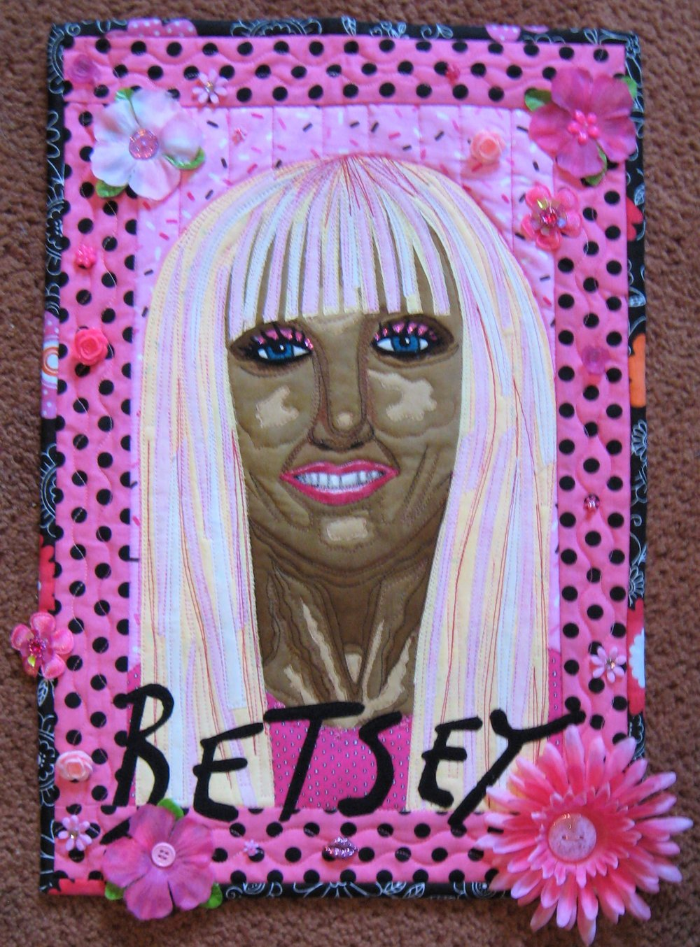 Today is reveal day for my Facebook art quilt group Art Quilts Around The World and the theme was Women Who Soar. That could be literal as in Amelia Earhart or a female pilot/astronaut. I perceived the theme as being inspired by a woman who has soared in her profession or personal life.    I selected the US fashion designer Betsey Johnson because she is my first influence in the 1970s regarding fashion and the fashion industry. I was sewing my own clothes back then in high school and discovered Betsey Johnson Butterick patterns. They had feminine details such as peplums, ruffles, puffy sleeves and bows. I was hooked on the patterns and Betsey's designs!!    Betsey has been a fashion designer for 40+ years and merchandizes clothing, jewelry, purses, eye glass frames, shoes and more. She has inspired me because of her use of hot pink, animal prints, flower/cabbage rose motifs, kissy lips, polka dots often combined with stripes and her use of girly ruffled garments including tutus! I have followed her career for many years and am also inspired by her ability to be a single parent to her daughter Lulu (she's grown now) while running a fashion design house as well as bounce back from financial hard times in 2008 when the financial state of the US was not good. Betsey always seems a bit too tan and she wears fake blond and/or colorful hair extensions while not pretending to be her real hair! She is 70+ years old and still does cartwheels after her showing at Fashion Week in New York City. I admire her zest for life and her ability to not have rules about ones age!! She seems to be having fun!   When I was choosing colors I used Betsey's signature hot pink  color which is on her merchandise labels, a variety of polka dot fabrics and as many pink rose and flower motifs from my embellishment stash. It is pink paradise and a tool to use when I teach about monochromatic color schemes!! I feel I can get crazy with a lot of embellishments if I stay in the same color family. I added Betsey's name in the font she uses on her merchandise-it's probably her own penmanship. All in all a fun challenge which was easy to do. Go Betsey and do not retire anytime soon!!