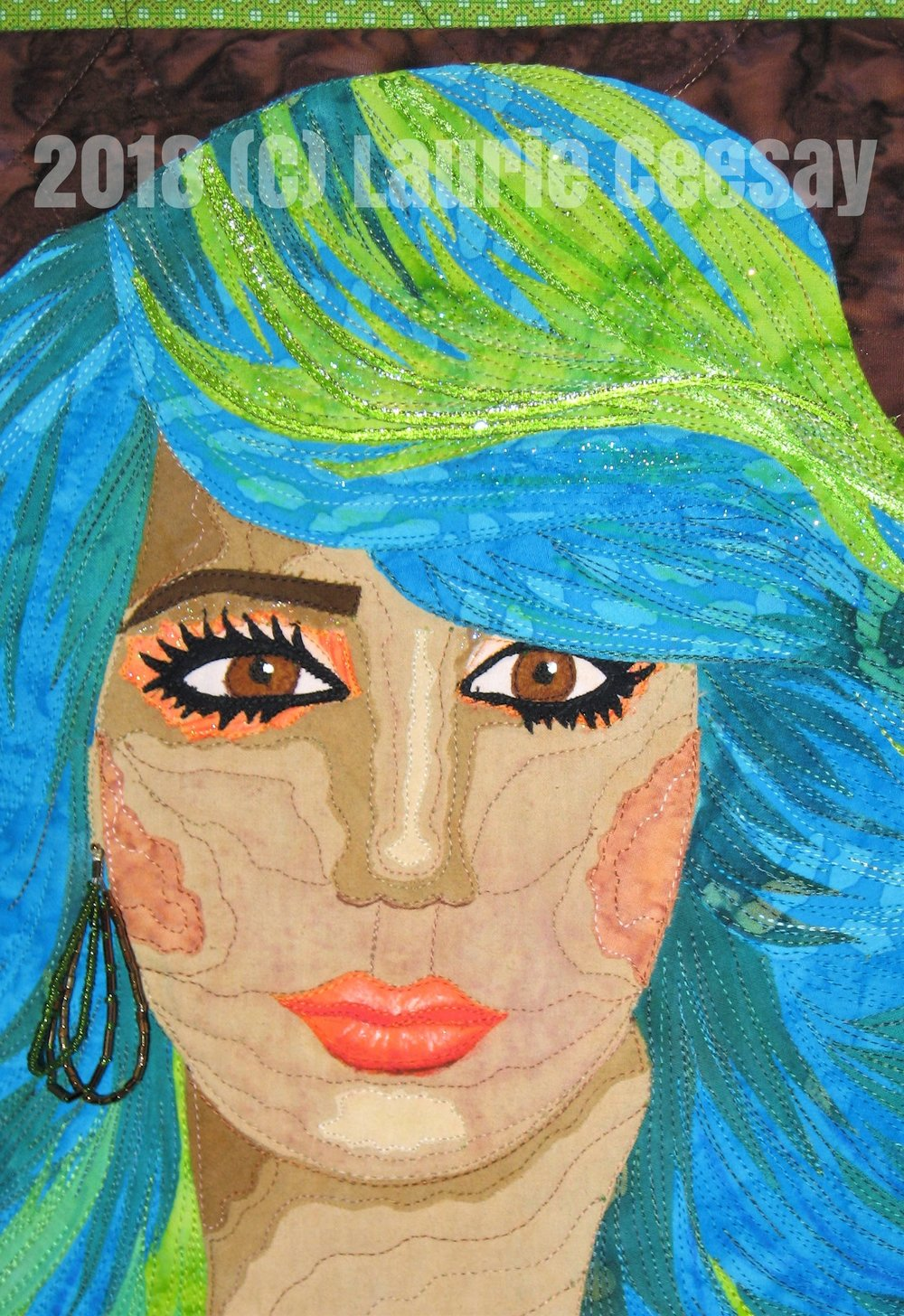 The face was embellished with fabric markers, fabric paint, glitter nail polish, and a real earring from my jewelry box. I intend to enter this quilt in a few quilt contests. When I find out when the TV show is ready for viewing on TV I will let people know.