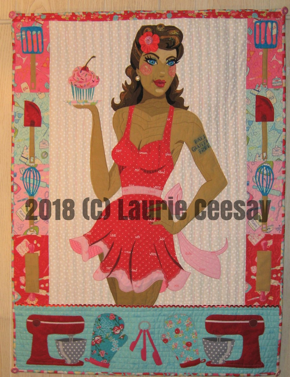 "The Wisconsin Quilt Expo is held in early September in Madison and they have been having a special challenge at their quilt expo and the theme for 2018 is called Bake Off. I immediately thought of a pin up girl in the kitchen when I designed this quilt. The only rule was the size of 30"" wide by 40"" long which is typically larger than I work. The pin up girl is wearing a sexy ruffly apron and holding a cupcake. I added baking utensils to the sides of the project to get the 30"" width. I added a wide bottom area with mirror images of a Mix Master, oven mitts and measuring spoons.  This project began with a purchase from www.craftsy.com where I purchased a variety of fabrics with a baking theme. I used a print with baking words in the apron, sash and bow. I added a red and white trim near the bottom edge.. The fingernails received red glitter nail polish."