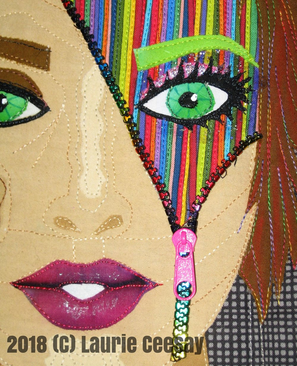 This is a close up of the face. The pink batik used in the mouth had a lot of muted stripes and I fussy cut the mouth applique to get shadow dimension and it turned out great without lots of work. The hair seemed to blend too much into the boring background so I used some lighter colored Derwent Inktense fabric pencils to add more contrast. I added some nail polish for eye glitter to the striped side of the face.