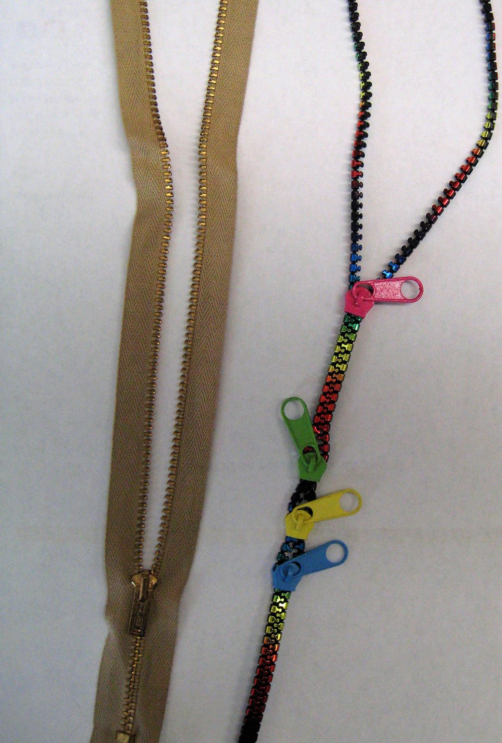 The zipper was hand tacked to the quilt when everything else was finished. I originally wanted to use the beige zipper on the left because I loved the metal teeth but the tape part was too wide and I couldn't see it fitting into the face area. The other zipper is something that I had in my stash. I think it is meant to be a bracelet. I chose to use the pink zipper pull because it is my favorite color.   When the quilt was finished I learned to love the idea behind the quilt.