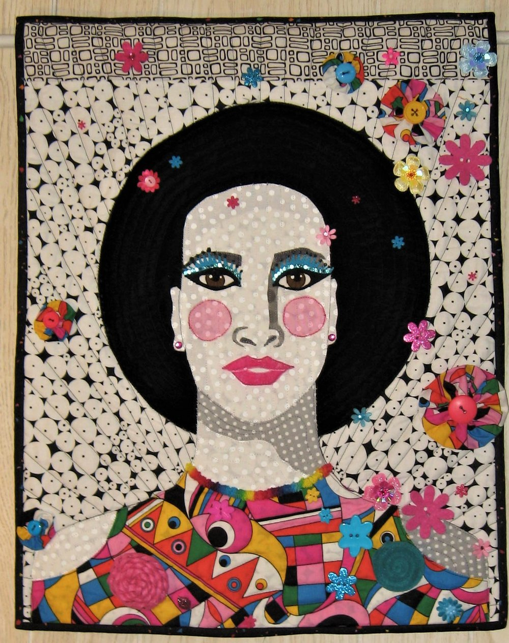 "I have had the pleasure of being selected as one of the ""Celebrity Quilters"" who have been asked to create a piece for the International Quilt Association's Mini Silent Auction quilted wall hangings which will be at the International Quilt Festival this November at Houston. These donation quilts help raise money for the association. I feel honored to be selected and am thrilled many thousands of people will view these quilts. It is hard to give this one up but I have the pattern if I want to make another version!!  I am loving Pop Art and found an image on Pinterest that inspired this quilt. I used velvet for the hair and mouth and pink tulle for the cheeks. I pulled many of my pink and turquoise flower embellishments and hand sewed them to this quilt. I have a fun rainbow trim that can be rusched by pulling the inner thread. I hand tacked some to the dress neckline. I made 5 fabric yo yos from the remainder of the ""mod"" dress fabric. The eyes were detailed with white matte fabric paint, brown Pigma Micron marker for the irises, black paint on the ends of the eyelashes and turquoise sequins glued to the eye for eyeliner."