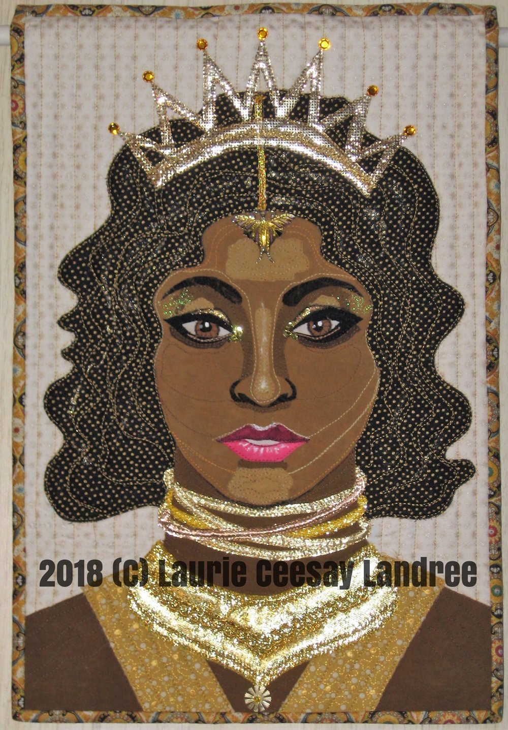 My Facebook art quilt group's current challenge is due for revealing today. The theme was Numbers but with a twist of using a song, book or saying title. I somehow had the Bruno Mars song 24K Magic pop into my head and I thought about a portrait quilt with the use of a bunch of metallic golds and a woman who represents an African/Nubian queen.  I pulled from my stash all potential lames and gold embossed fabrics. I wanted a crown on the woman's head and a lot of necklaces and a collar type thing around her neck. I frequented Pinterest for ideas and ran with what I liked.  I embellished this quilt with a sequin/bead, chunky gold glitter, gold nail polish, gold Dollar Store poster paint, fabric markers, white matte fabric paint, rhinestones, grosgrain ribbon and a repurposed earring hanging on the forehead. I had more than enough trim and bling to make this work so I had to edit out some of the goodies.