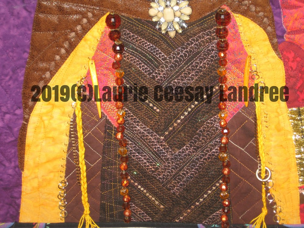 "The garment required plenty of handstitched bead application, use of my fancy sewing machine stiches, embellishments from embroidery floss, jump rings, repurposed pieces from jewelry and the ""belt buckle"" was a large bracelet piece from a friend who gifted me her ""junk"" jewelry!! I usually devote lots of time to the make up and have to add bling. This warrior woman didn't need this but I added a tiny bit on the center piece of the garment to ""Laurie-ize it!"""