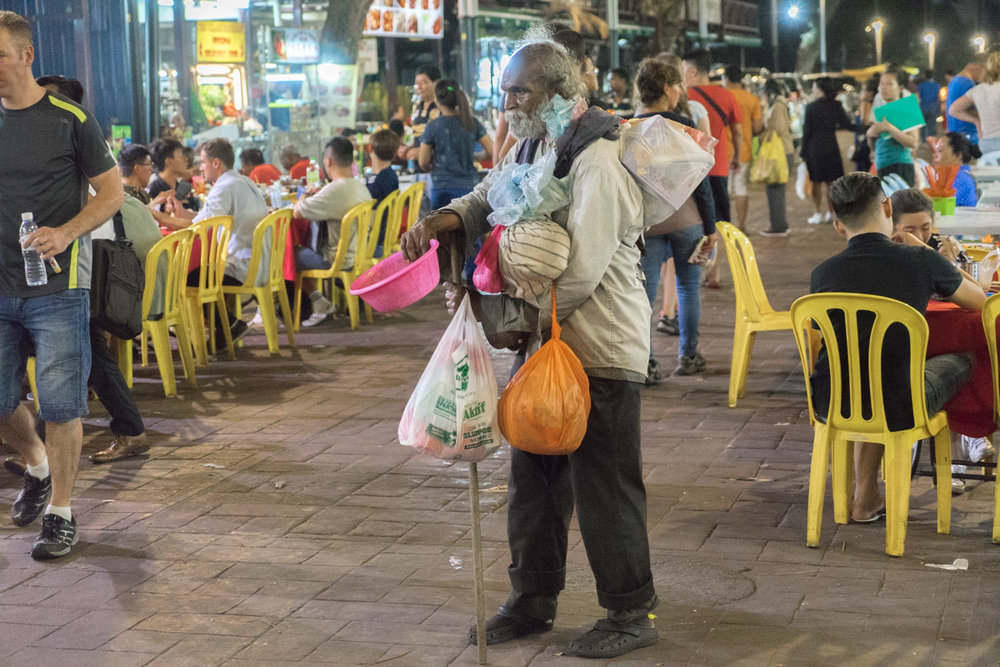 One of the many people walking through the Alor Street Food Market at night
