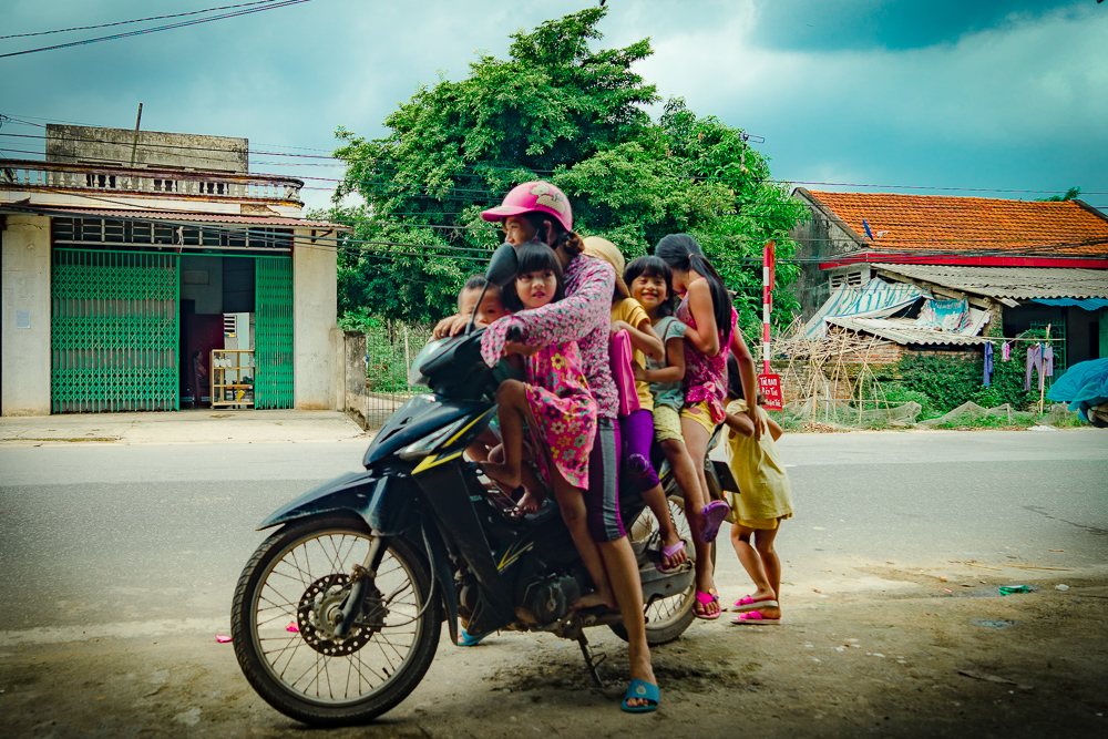 1 motorbike, 1 adult and 6 children without helmets. Survival of the fittest/luckiest in Vietnam!