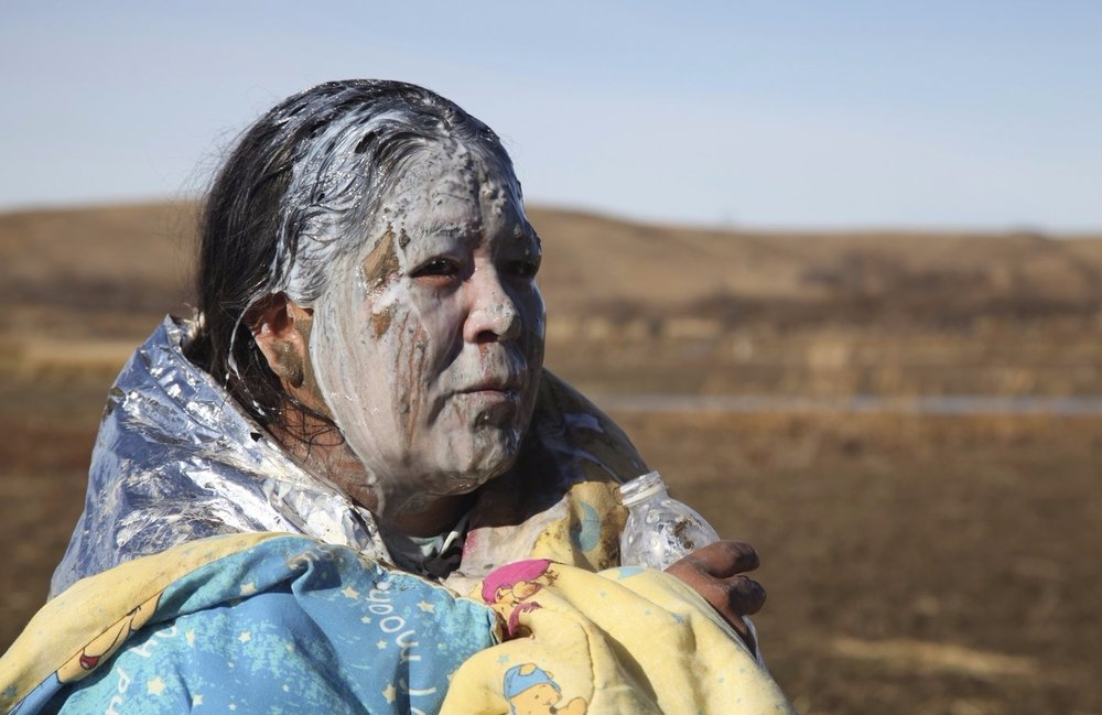 John L. Monroe/AP image taken from NPR  This is an image of Tonya Stands Recovering from being pepper sprayed by police. Stands and other protesters swam across a creek hoping to peacefully block construction of the Dakota Access Pipeline. The Dakota Access Pipeline has been highly protested and contested since its proposal in June of 2016 because the natural gas pipeline is to built on sacred tribal land and negatively impact the Missouri River, which is also the main water source for the Standing Rock Reservation. The story of the Dakota Access Pipeline is not unique it is a centuries-old fight for indigenous people to protect the land and their rights from colonizers.