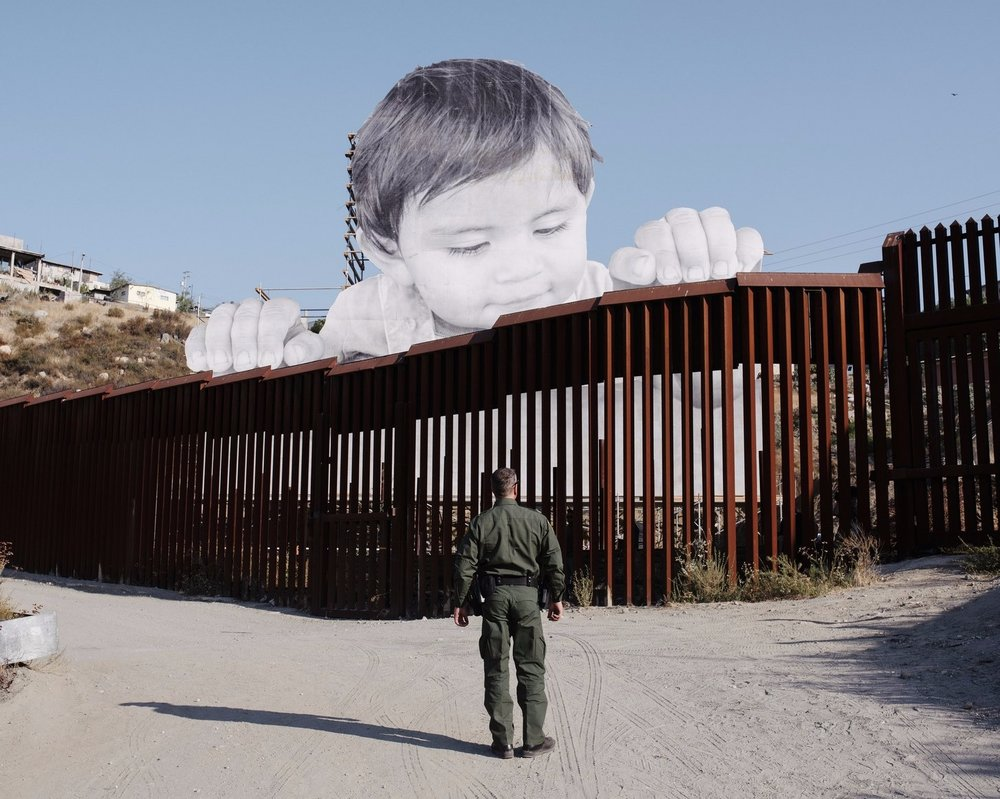"Photo by John Francis Peters NYT vis Redux and The New Yorker  The French artist JR's newest art installation is a child peaking over Trump's border wall in the Mexican city of Tecate to stare at US boarder patrol. The artist states that the child, Kikito, lives next to the wall and his inspiration came from seeing the child peak out from the slats in his crib while the artist chatted with the mother. Upon seeing a rendering of the installation the child's mother stated ""I hope this will help people see us differently than what they hear in the media, that they will stop thinking of us like criminals or rapists. I hope in that image they won't only see my kid. They will see us all.""   Quote from 'The New Yorker', 'The Artist Jr Lifts a Mexican Child Over the Boarder Wall' by Alexandra Schwartz (September 11th 2017)"