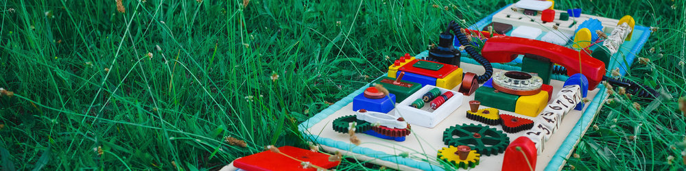This busy board from Etsy is colorful and super fun. It combines many practical life activities that enhance motors skills along with creativity.