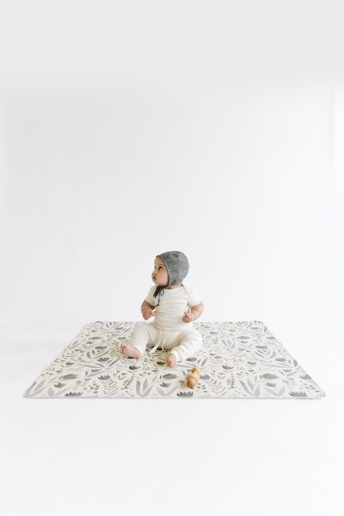 Baby sitting on a leather mat, perfect for Montessori play that involves the whole for young infants.