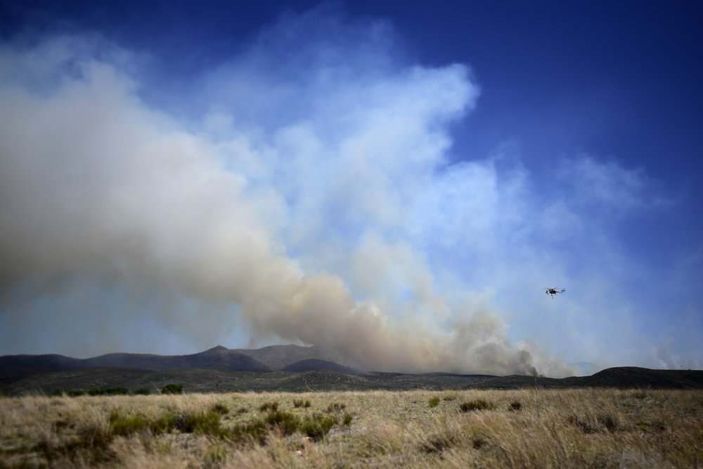 A helicopter flies over plumes of smoke to pour water on flames about 60 miles northwest of Phoenix, Arizona, on Thursday, June 9, 2016. The fire forced roughly 300 evacuations in a community where a 2013 fire killed 19 members of an elite firefighting crew.