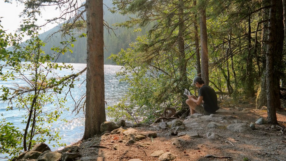Taylor relaxing at the edge of our campsite while enjoying a view of Lake Bowman
