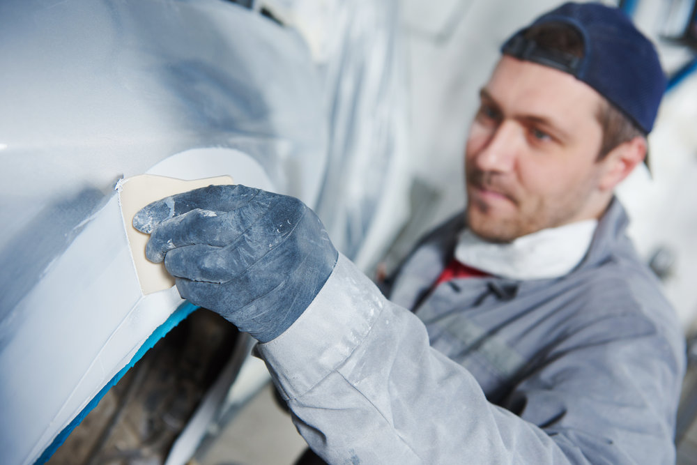 Worker doing auto body repair on an vehicle.