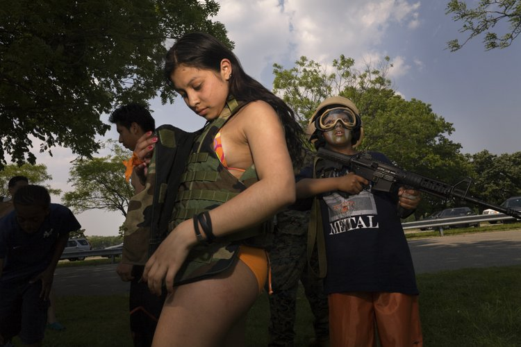 USA, NY, Bronx, Orchard Beach, 2007, Marines land attack helicopters, paint children in camouflage and unfurl infantry weapons, including pistols with silencers for the public's amusement with the unspoken aim of recruiting new marines.