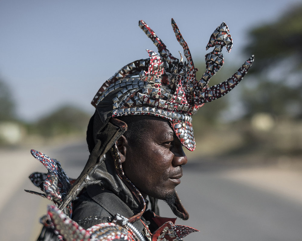 Botswana, Ghanzi, May 2017,He is in the festival with his friend Ralf, they say, they are brothers. They manufactured their costumes by themselves. The suitcases belong to the outfit (but they are empty).