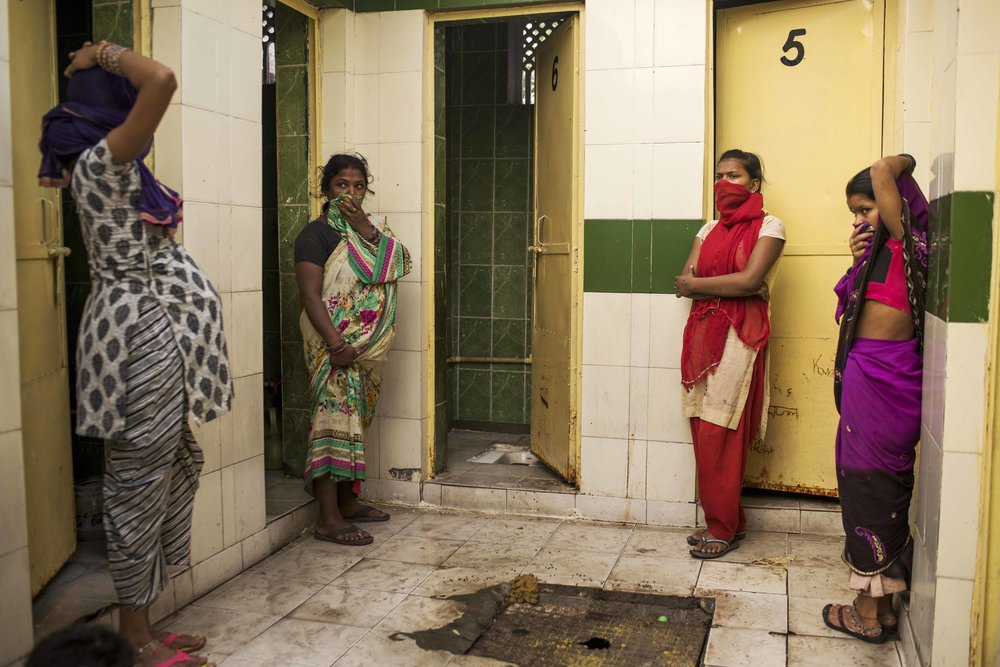 India, New Delhi, October 2016, Community toilets are one answer to India's lack of toilets. But without a system for maintenance and cleaning, defecation remains a health problem. These four are waiting for the one open, working stall to open for use.