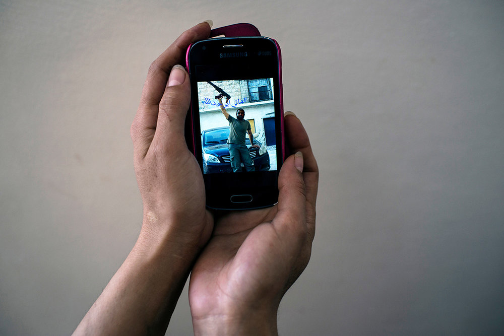 """When her husband  was alive, he would send """"Aysha"""" sultry texts, poems, and fighter images from the front lines. It was by text message she found out that he died while fighting in Syria. When her old nokia died, she lost her trove of memories. This is the only image she has from that time before his death."""