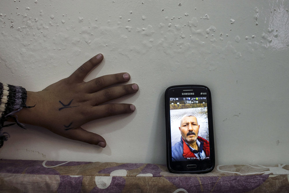 """Jordan, 2014,Muna, a Syrian """"urban refugee"""" and female head of house shares photographs of her husband from Germany. 'I swear each photo of him standing in the sun, or by an old church...you see devastation and guilt on his face. He wants to be with us so badly. We survive off of this photos and the lullabies and love messages he sends us on whatsap.' Her daughter's hand reaches for phone."""