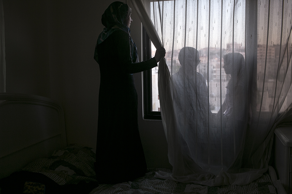 Jordan, 2015, Myriam is a 23-year-old widow of three young children struggling to survive as an urban refugee. She is luckier than most, she has found a job in a salon. She also does not discuss the torture and rape she endured on the outskirts of Damascus. She waits until her kids are asleep to break down and cry. She is determined to never let them know what she suffered. Here she has enough for the rent, barely. But she can't fathom a future for herself or children in an unchanging status quo.Two of her three children are pictured:Lara, 7, and Muhammed, 6