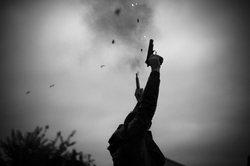 Guns are fired in the air to celebrate the wedding party for Medina Khamkoyeva.