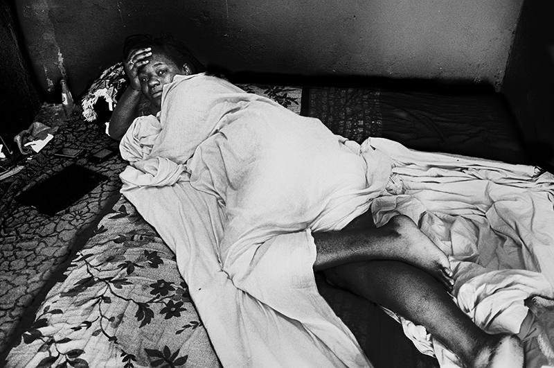 D.R. Congo, Kinshasa, October 2011. A young woman lies on her bed in the afternoon heat.