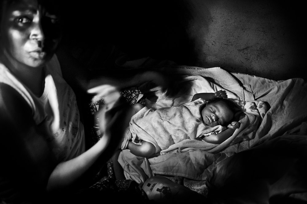 D.R. Congo, Kananga, October 2011. A mother and her newborn son during a power cut inside the Kananga hospital.