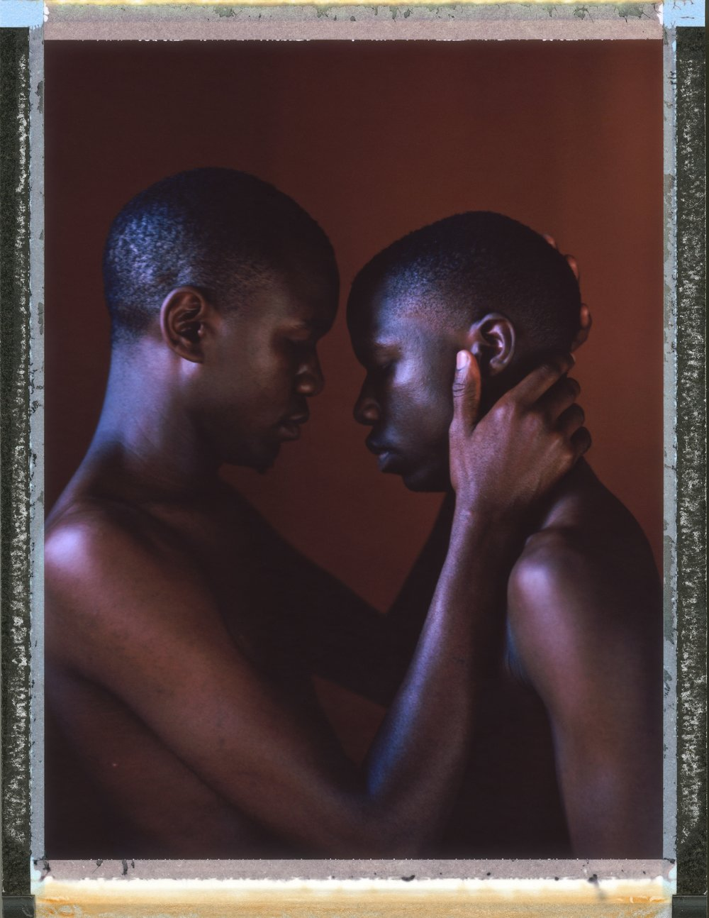 "A posed portrait of 25 year old Miiro (left) and 21 year old Imran (right, not his real name), a gay couple living together in Uganda. Miiro, describes their eviction from their home because, he says, they are gay: ""We heard people stoning the door and windows while shouting, telling us to immediately leave the house because they were tired of us, claiming that we are curse to the village, and even to the teenagers in the village… After a while of storming the door, it broke and we were pulled out, thrown on the ground, beaten and flogged for almost an hour. We were half dead. And they burnt all things in the house in the process. The leader of the village intervened and they decided to take us to the police station for life imprisonment."" Miiro spent four days in police cells before being released by human rights lawyers. He went into hiding for two and a half months. He received $160 relocation money from a non-governmental organization but he says it wasn't enough to start a new life. Even before their eviction though, life as gay men in Uganda was not easy. has faced constant persecution because of his sexuality. He describes being 'outed' at school, and the moment his mother found out: ""She didn't even have to listen to what am to say, she told me I was a disgrace and I wasn't worthy being her  son, she went ahead to disowning me there and then in front of the entire school and its staff and that I would rather be dead than having me alive as gay. She then walked away and left me on my knees begging for her at least listen to what I have to say, the head teacher then asked me to leave his school, I left school while being mocked , laughed at, on that day hated myself to the extreme I felt I wasn't worthy living, where was I to start from? How when the only person I trusted in the world turned her back on me? And this was the beginning of my suffering."" Uganda, September 2014.  While many countries around the world are legally recognizing same-sex relationships, individuals in nearly 80 countries face criminal sanctions for private consensual relations with another adult of the same sex. Violence and discrimination based on sexual orientation or gender expression is even more widespread. Africa is becoming the worst continent for Lesbian, Gay, Bi-sexual, Transgender, Queer, Inter-sex (LGBTQI) individuals. More than two thirds of African countries have laws criminalizing consensual same-sex acts. In some, homosexuality is punishable by death. In Nigeria new homophobic laws introduced in 2013 led to dramatic increase in attacks. Under Sharia Law, homosexuality is punishable by death, up to 50 lashes and six months in prison for woman; for men elsewhere, up to 14 years in prison. Same sex acts are illegal in Uganda. A discriminatory law was passed then struck down and homophobic attacks rose tenfold after the passage of the Anti-Homosexuality Act. In Cameroon it is also illegal. More cases against suspected homosexuals are brought here than any other African country. In stark contrast with the rest of the continent, same sex relationships are legal in South Africa. The country has the most liberal laws toward gays and lesbians on the continent, with a constitution guaranteeing LBGTQI rights. Because of this, LGBTQI Africans from all over the continent fleeing persecution have come to South Africa. Despite these laws, many lesbians have been victims of 'corrective rape' and homosexuals have been murdered for their sexuality. Homophobia is by no means just an African problem. In Russia, politicians spread intolerance. In June 2013 the country passed a law making ""propaganda"" about ""non-traditional sexual relationships"" a crime. Attacks against gays rose. Videos of gay men being tortured have been posted online. In predominantly Muslim Malaysia, law currently provides for whipping and up to a 20-year prison sentence for homosexual acts involving either men or women. Increased extreme Islamification in the Middle East is making life more dangerous for gay men there, as evidenced by ISIS's recent murders of homosexual men. While homophobic discrimination is widespread in Lebanon, life is much safer there than Iran, Iraq, and Syria from which refugees are fleeing due to homophobic persecution. Photo Robin Hammond/NOOR for Witness Change"