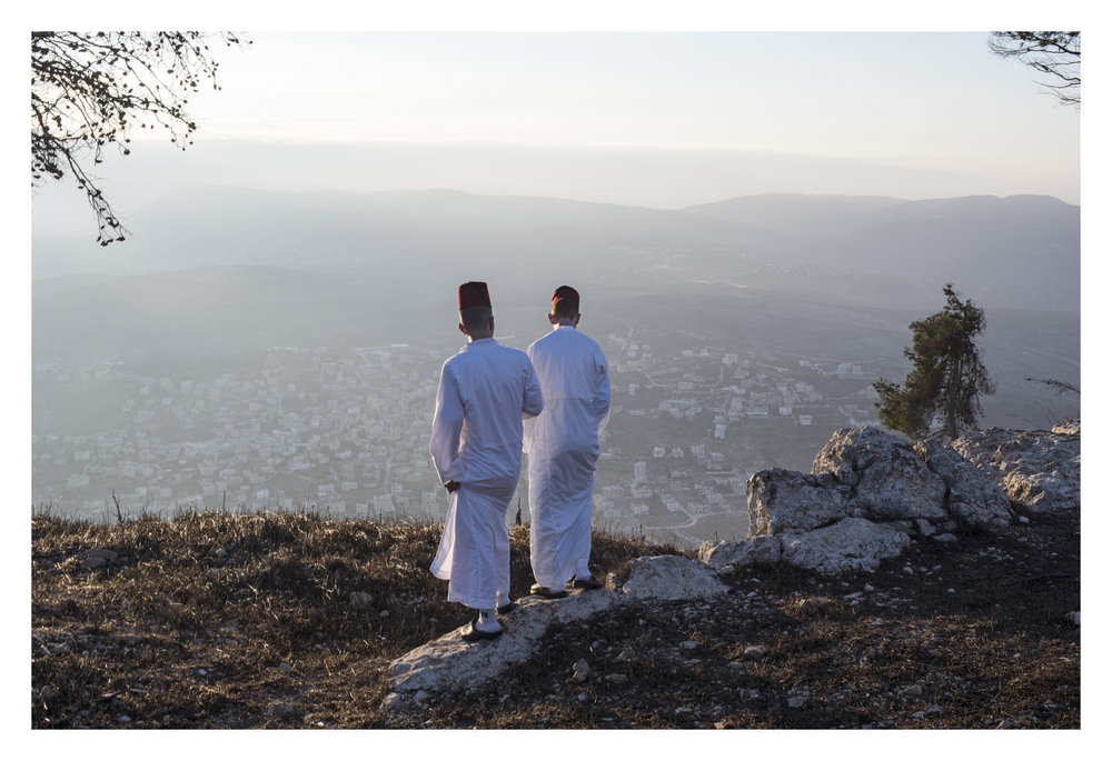 After the final prayer with book , youth of assorted ages and men take a pause on mountain and relax, overlooking the view of mountain after sunrise. Here, they are standing near the enclosed area they say is where Isaac's father was tested for sacrifice. (daniel, please read)
