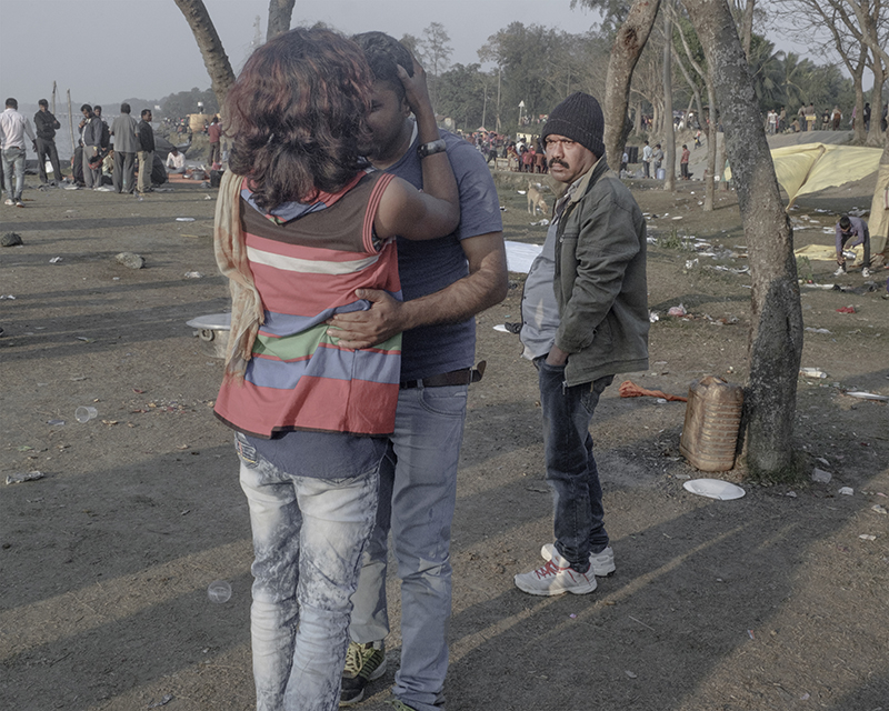 India, Falta, January 2017. A transgender individual obliges a drunk picnicker under the disapproving glances of another man. A group of transgender persons went about the crowds usually to dance with them in exchange for cash.