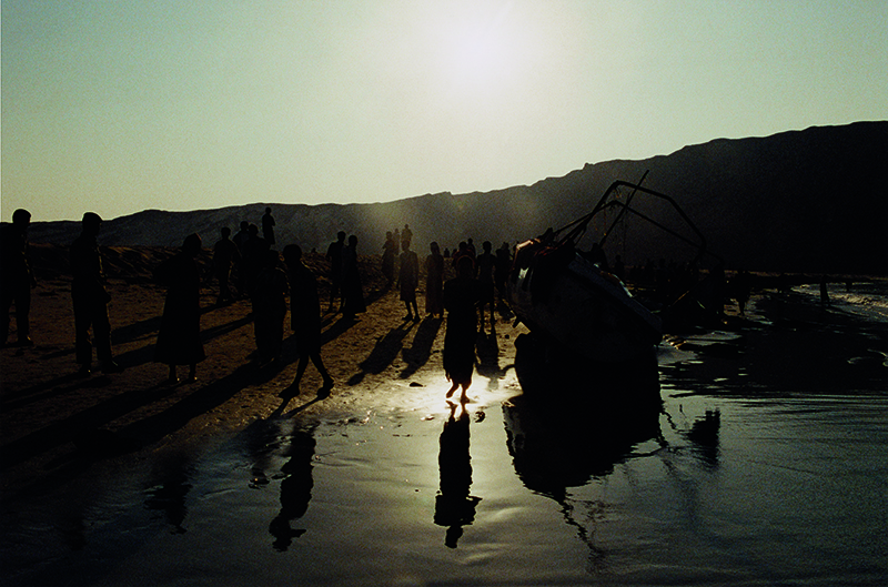 Bir Ali, Yemen - May 2007. Having arrived in the middle of the night following a fifty-seven hour long voyage from Somalia, dawn breaks over a group of Ethiopian migrants and refugees at a sandy beach near Bir Ali on Yemen's southern coast.