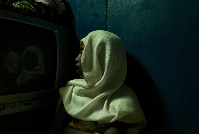 Djibouti, Djibouti, March, 2008. Nine year old Kali Abduhi Omar stares at her reflection in the screen of a broken television set as she sits in a make-shift room in one of Djiboutiville's illicit doss houses.Following a mortar strike on her family's home in central Mogadishu, Kali and her younger brother have just arrived in Djibouti after spending weeks on the road in a bid to escape Somalia.