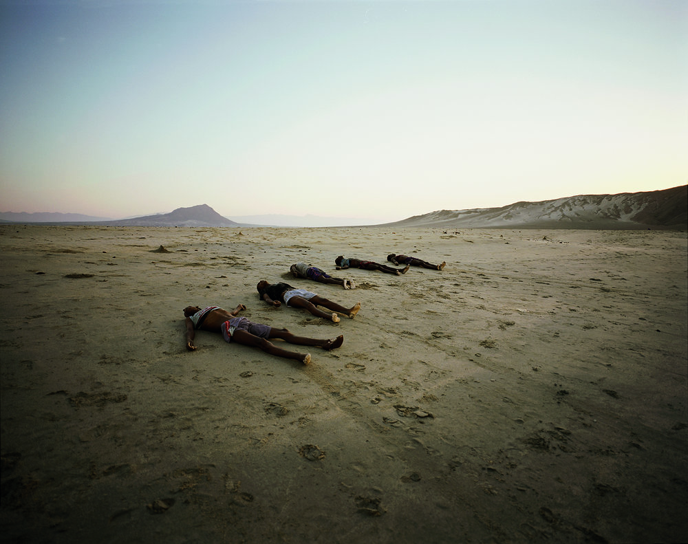 Bir Ali, Yemen, May, 2007. Having been washed ashore with the morning tide, a row of corpses line Al-Baida Beach at dawn. Hauled from the water by fellow voyagers, a total of thirty-four bodies were found at sunrise as they slowly drifted inland. Just one week after an almost identical tragedy saw thirty dead on a nearby beach, Somali smugglers continue to drop their human cargo out at sea without regard for life rather than coming close to shore and risking detection. Having paid a million shillings each, for the survivors that have now finally made it to Yemen, the realisation of just what a gamble they have taken with their own destinies hits home. Most sit weeping, having spent the night looking for lost relatives, or simply in shock at the mortality that surrounds them.