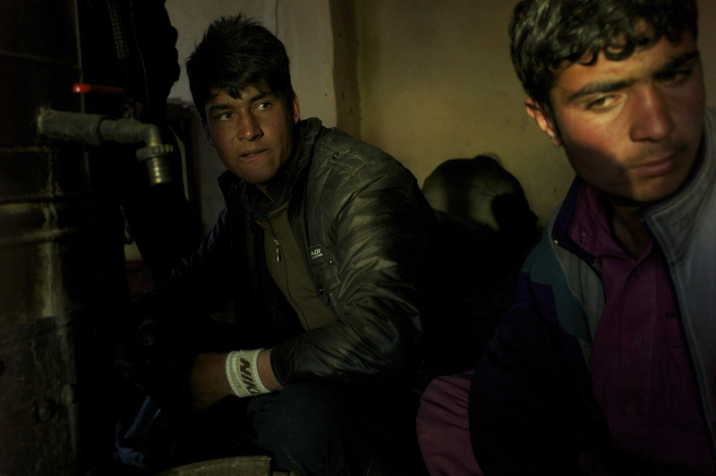 Afghanistan, Kabul, February 2012, Arriving in Kabul from Logar province, seventeen year old Farshad settles down beside a bukhari stove at the Palawan Ghani Mosafer Khana, set back from the mud and chaos of the Company district bus station.