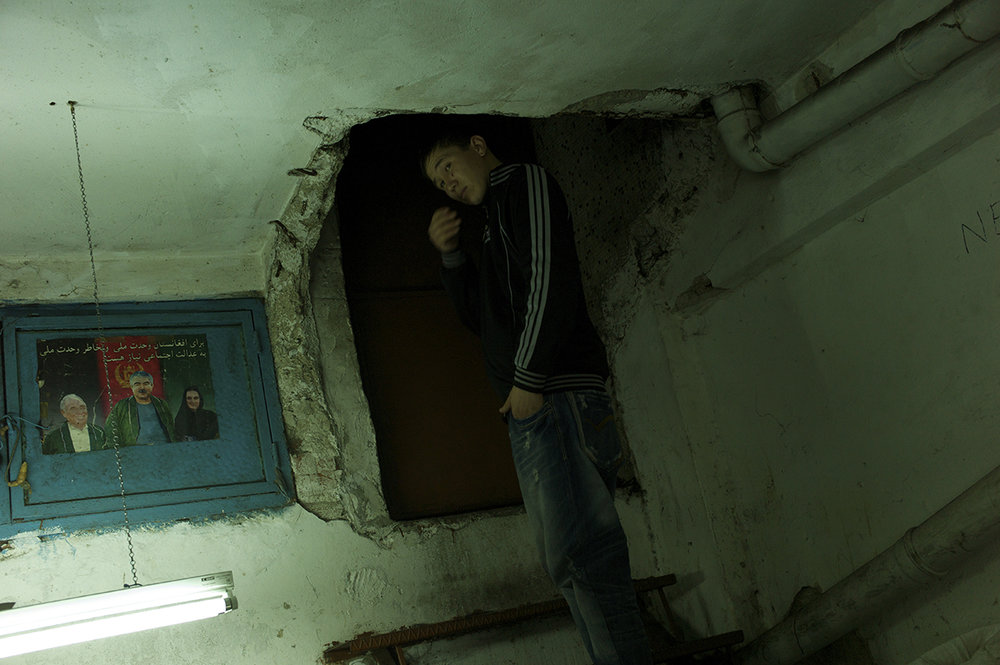 Turkey, Istanbul, January 2012, Finishing his shift at close to midnight, sixteen year old Imamuddin heads out up a metal stepladder through the carved-out entrance to the underground kargah in Zeytinburnu where he has recently found work.