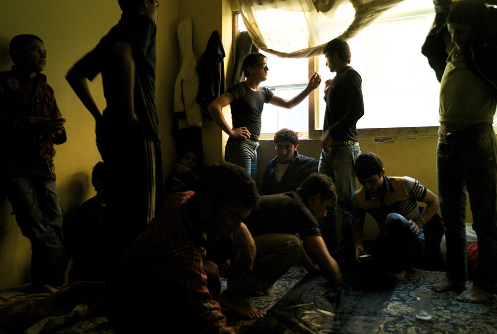 Greece, Athens, October 2011, As lunch winds down and the plastic mat that is used in place of a table is folded away, eleven year old Baseer leans against the wall, watching as the older boys retreat to the window to smoke a joint.