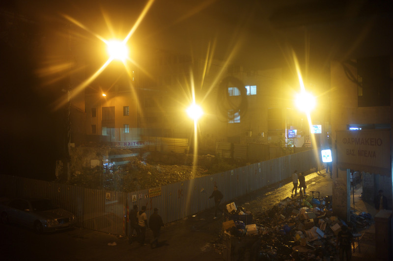 """Greece, Athens, October 2011, Seen through the window of a Pashtun smuggler's café known simply as """"Bashir PCO"""" after the international call centre across the road, piles of rubbish sit piled up at a junction on Omonia's Xouthou Street."""