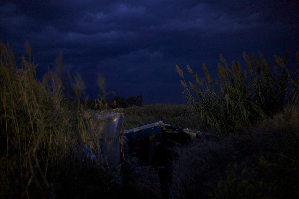 Greece, Patras, October 2011, Strong winds blow through the pampas grasses surrounding a crudely built shelter just illuminated by the glow from the nearby Silk Road petrol station at night, at a spot known locally to Afghans as Pump Benzene Camp.