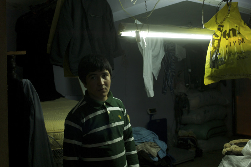 Turkey, Istanbul, January 2012, Next to a mattress balanced over the basement stairs, fourteen year old Abdul Hashim stands amid the cluttered storeroom in the kargah where he has spent the past months cutting cloth.