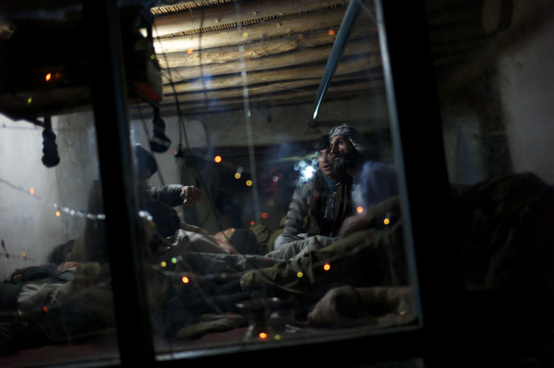 Afghanistan, Kabul, March 2012, Behind a cracked windowpane strung with fairy lights, a few passengers who are unable to sleep watch a game of football on a television set surrounded by rows of bodies passed out under sheets.
