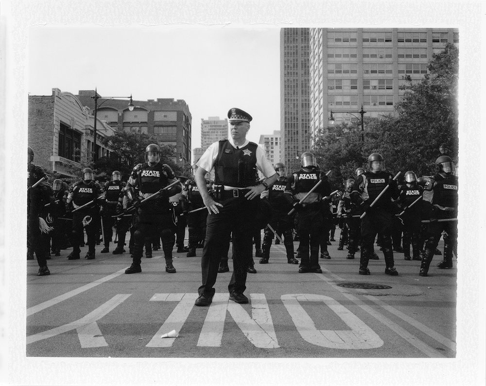 A Chicago Police officer stands in front of his men waiting to give the orders for the crowd of protesters to disperse.