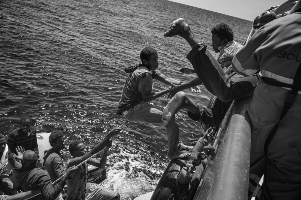 Migrants on board of a sinking rubber dinghy carrying 95 people climb on board a rigid-hulled inflatable boat (or RIB) launched by the MSF the Bourbon Argos search and rescue ship patrolling the SAR zone of the Mediterranean Sea. 21 August 2015.