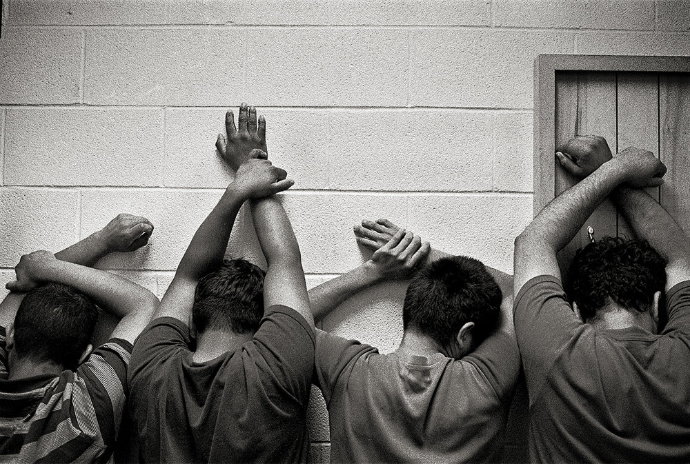 USA, McAllen, January 2005, After being processed in the Border Patrol headquarters, detained migrants are searched for contraband or weapons, put on a bus and sent to a detention facility. They had to keep their arms up the whole search, which lasted nearly 45 minutes.