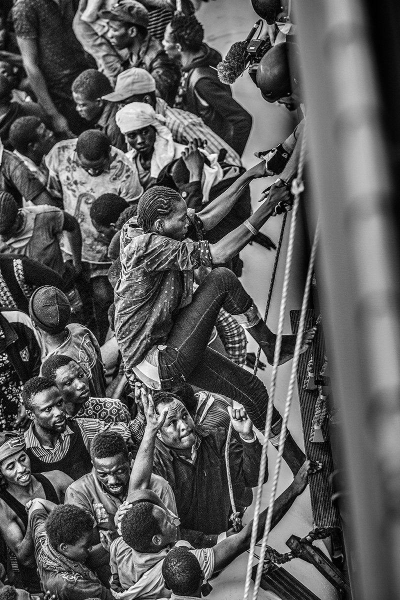 Mediterranean Sea, 26 August 2015, Migrants on board an overcrowded rubber dinghy sailed from Libya are transferred onto the MSF Bourbon Argos. After the second rescue of the day, the Argos has more than 700 migrants on board.