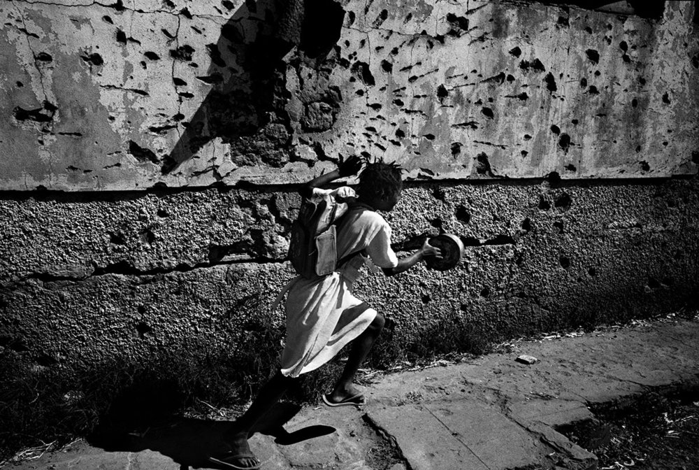 Angola, Kuito, June 2002. A girl running in front of a building which used to be the school.