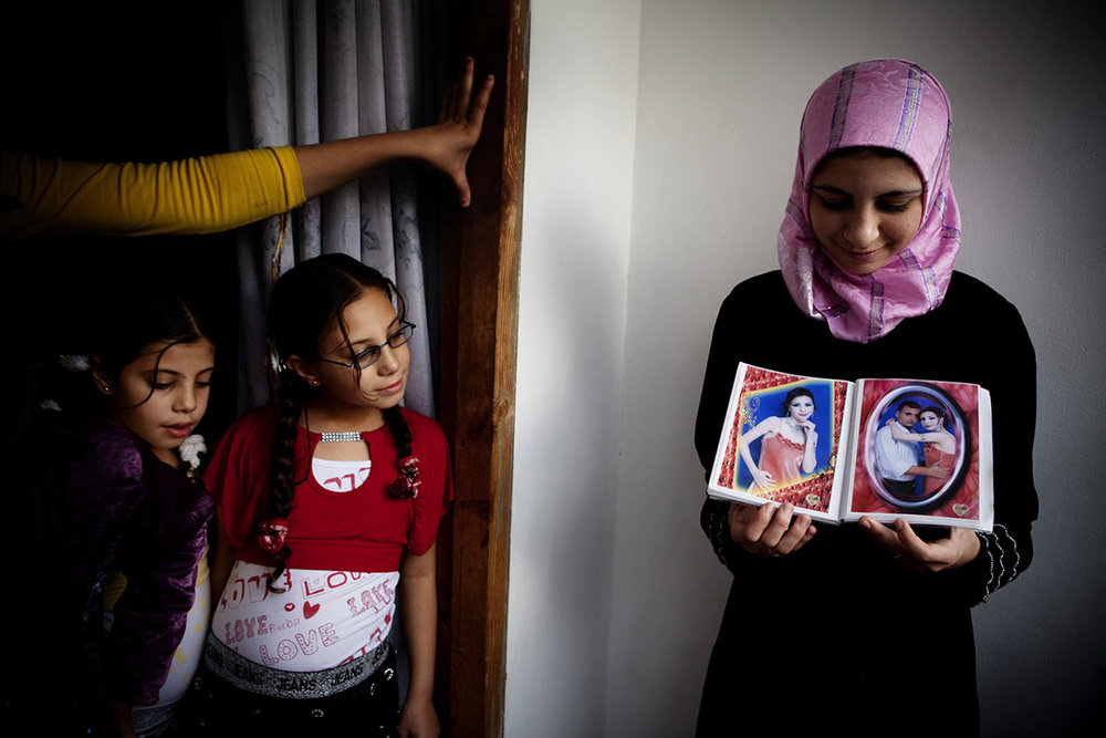 Occupied Palestinian Territories, Gaza City, October 2009, In the Gaza City home of Dr Jamal Shareef, a literature professor at Al Azhar University, his 16-year-old niece (right) shows pictures of her fiancé.