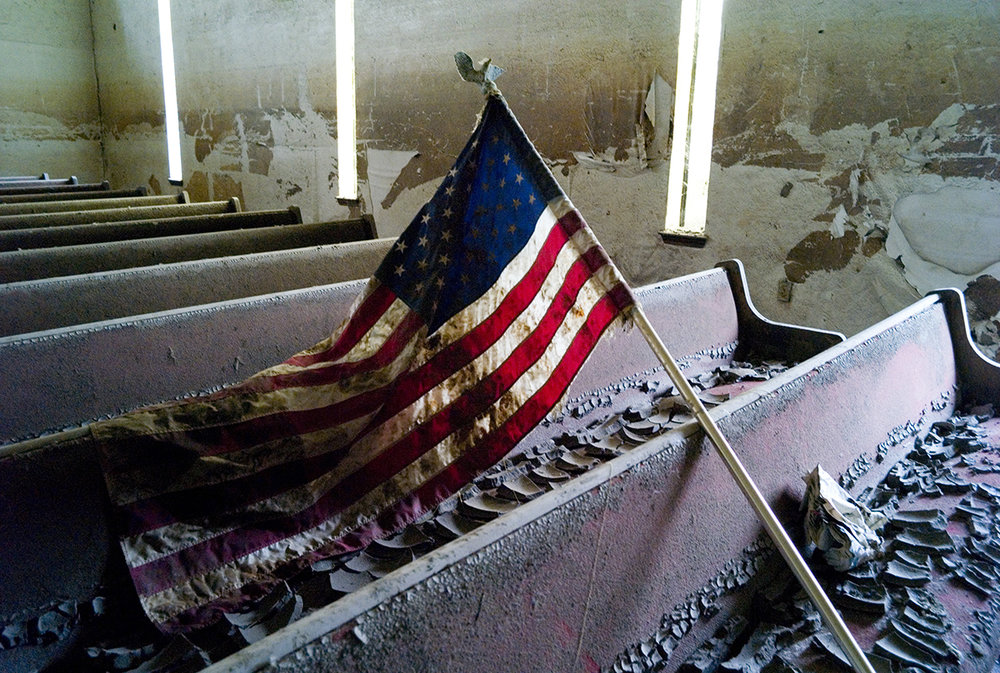 USA, New Orleans, 2007, A Katrina mud covered flag is strewn in a church in the lower 9th ward. No one has begun to clean it up or renovate it.